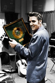 Elvis Presley holding framed gold record of Heartbreak Hotel while in an unident. recording studio to record a new song.