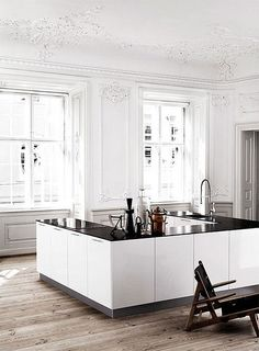 The contrast between the classic details on the ceiling and walls and the minimalist kitchen is very original! Beautiful!
