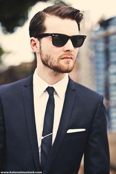 Shop this look on Lookastic: http://lookastic.com/men/looks/sunglasses-dress-shirt-tie-pocket-square-suit/9407 — Black Sunglasses — White Dress Shirt — Navy Tie — White Pocket Square — Navy Suit