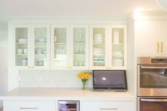 A kitchen in suburban Detroit uses modern slab-style cabinets with traditional touches to achieve a very inviting and warm feel. Warm Kitchen, Brass Kitchen, Kitchen Shelves, New Kitchen, 1960s Kitchen, Mid Century Modern Kitchen, Cedar And Moss, Modern Shelving, Cabinet Styles