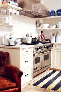 White kitchen with chrome oven and open shelves with blue bowls
