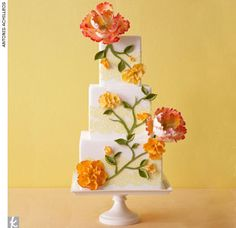 Square wedding cake with oversized sugar flowers and yellow lace-like trim by Truli Confectionary Arts.