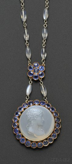 Fine Jewelry - Sale 2586B - Lot 575    Moonstone Cameo, Moonstone, and Sapphire Pendant Necklace, c. 1920, the moonstone cameo depicting the bust of a maiden, framed by circular-cut sapphires, and suspended from a circular-cut sapphire cluster and barrel-shape moonstone bead chain, gold mount, pendant dia. 1 3/8, chain lg. 24 3/4 in.   Sold for $14,220.00