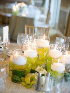 Candles floating in water with green leaves underneath. Soft lighting for table decor