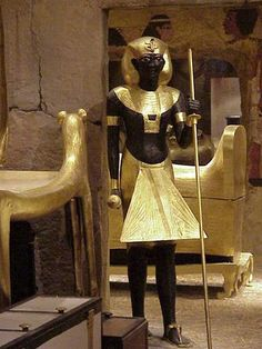 This statue depicts an Egyptian man that is wearing a Schenti (a wrapped skirt around the waist), a decorated apron, possible gold bracelets and armlets, a wesekh collar (a decorated, traditional rounded collar), sandals, no evident hair or makeup, and a uraeus headpiece (a headdress with a cobra).  It can be assumed that this man is in the upper part of the Egyptian social status, possibly as a court official or a noble.