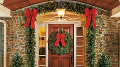We love the look of lit greenery framing an entrance. Bright red bows complete the festive display. - Photo: Courtesy of Frontgate