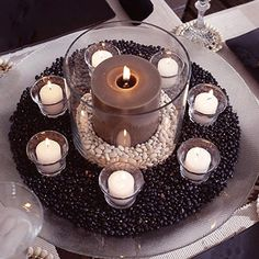 thanksgiving centerpiece: place pillar candle in a lg glass cylinder, pour dried white beans into cylinder, fill about 2 in deep. place cylinder in a wide glass bowl and pour dried black beans around it. surround cylinder w white candles in glass votive cups