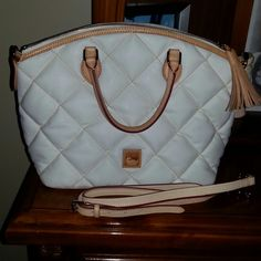 Dooney & Bourke This bag has a quilted look. It is white with light brown handles. Has a light tassel attached to the zipper. Red on the inside with a small zipper pocket and 3 other small pockets. In great condition.  Has a shoulder strap and key holder. Dooney & Bourke Bags Satchels