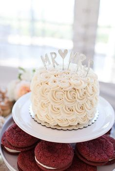 Simple single tier wedding cake with buttercream rosettes and cute cake topper