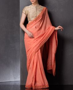 Peach sari with floral embroidery adorning the pallu and pleats. Crochet border across length. This sari comes with golden blouse featuring prints and metallic work adorning the round neckline and front. Short sleeves. Wash Care: Dry clean only