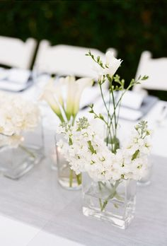 All-white blooms, including elegant calla lilies, were placed in simple glass containers of different shapes to create a polished centerpiece setup.