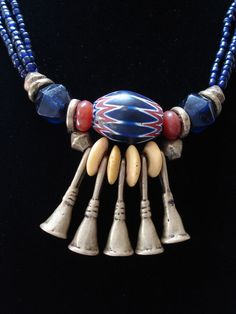 By Luda Hunter | Necklace; A three strand necklace of old cobalt blue Naga glass beads, combined with a pendant that came together using an old 6 layer Chevron bead from the African trace, 2 antique Carnelian beads, old cobalt blue cornerless Bohemian glass beads, yellow disc African Trade beads, Nigerian brass beads and 5 brass trumpets.