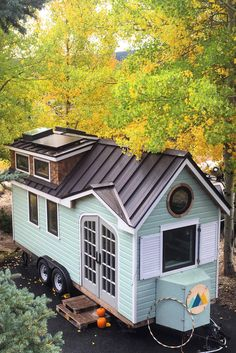 This tiny house has beautiful French doors, a large living room with a wood burning stove, and a kitchen with an apartment size refrigerator.