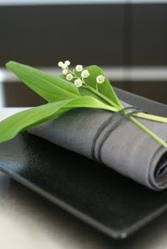 elegant - lily of the valley on black.my favorite flower even! Love the simple elegance of this look Shades Of Green, Green And Grey, Simple Elegance, Elegant, Beautiful Table Settings, Napkin Folding, In Vino Veritas, Deco Table, Lily Of The Valley