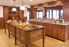 Shaker style Crown Point kitchen featuring a stunning oversize island with turned legs. Handcrafted from Cherry.