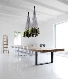 diy wine bottle chandelier, reclaimed wood table with metal strap legs and ghost chairs. minimalist design all white room makes the furniture the star Diy Bottle Lamp, Wine Bottle Chandelier, Diy Chandelier, Pendant Lamps, Chandelier Creative, Pendant Lights, Pendants, Lampe Salon Design, Design Transparent