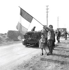 A French veteran greets Canadian vehicles, July 1944. LIEUT. G.A. COOPER, LIBRARY AND ARCHIVES CANADA—PA131386