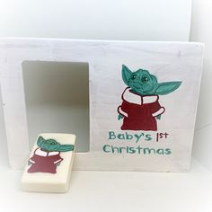 """Just in time for Christmas. We have a super adorable Set that includes a Hand-Painted Baby Yoda Wooden Frame with 3"""" x 4 1/2"""" opening (with glass cover) for a photograph, and a Baby Yoda Soap. The hand-painted frame is hand-painted with the words """"Baby's 1st Christmas"""" and a Baby Yoda on the front. WE ARE OFFERING A FREE NAME PERSONALIZATION AND WE WILL ADD THE YEAR AT NO COST TO YOU. The soap is 2"""" x 3"""" and is hypoallergenic. The soap is hand-painted with Baby Yoda."""