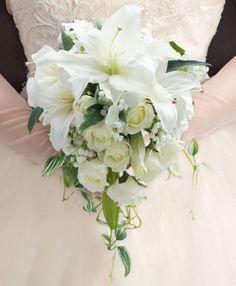 【作品について】  二人の新しい門出を祝う結婚式。ゲストの視線の真っ先に飛び込んでくるのは何でしょうか?ドレスやヘアメイクも素敵です、でも、やはり花嫁が持つブーケではないでしょうか…花嫁を寄り一層美しく見せてくれるブーケの王道・キャスケードブーケ。流行に左右されないキャスケードブーケはいつの時代も花嫁やゲストを魅了してきました。カサブランカ・ローズをたっぷり使っているので豪華・華やかさ・美しさ・可憐さ…全てを盛り込んでいます。花材はアーティフィシャルフラワーを使用していますが画像はまるでフレッシュフラワーのような瑞々しさもありますね。ホワイトドレスとの相性抜群なのでブーケ選びに迷ったら是非当サロンのキャスケードブーケをご指名下さい♪【サイズ】 幅・奥行き約25~30cm長さ・約45cm【素材】 ・アーティフィシャルフラワー・サテンリボン ・コサージュピン【付属品】 ・ブートニアをセットしています。※受注製作です 。