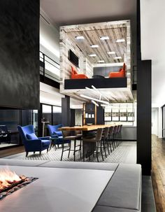cool hang out space. like the blue chairs, fireplace, and long table (a long island would work for eating space too.