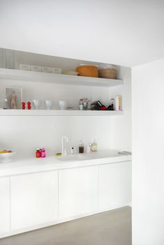 A Family Apartment in Italy, Modern Classics Included : Remodelista - white super minimal kitchen with bright accessories