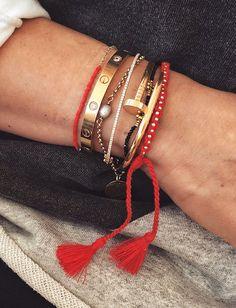 Bracelets dorés + bracelets précieux + liens rouges = le bon mix