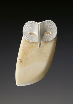 A silver and fossilised walrus-ivory brooch by Kristin Mitsu Shiga in the form of a barn owl; the owl is today a symbol of wisdom and knowledge.