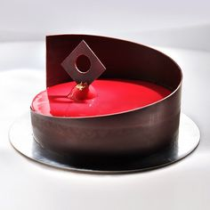 Cake with bananas and chocolate. Decor dark chocolate and red mirror glaze.