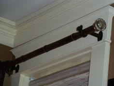 Master bedroom curtain rods made from bamboo poles with 1940's glass door knobs for ends.