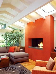 A vibrant tomato bisque-hued plaster added to this fireplace remodel turned the hearth into a modern showpiece in this living room. Interior Exterior, Interior Design, Living Room Orange, Orange Rooms, Modern Fireplace, Fireplace Wall, Basement Fireplace, Fireplace Update, Simple Fireplace