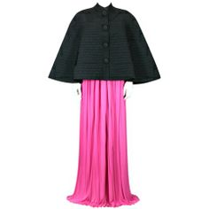 Rare Schiaparelli Black Quilted Faille Evening Cape, 1951 over her hot pink skirt.