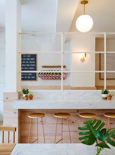 Pink accents contrast the pale palette that US firm ASH NYC has used for the interior of Dig-Inn restaurant in Boston.