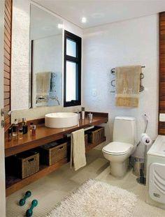 """Banheiro simples, neutro e """"clean"""". Cerâmica branca do chão ao teto.      Aí temos uma cerâmica efeito cimento, e um armário em tom int..."""