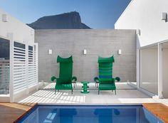 Terraço debruçado sobre cartões-postais | As belas cadeiras verdes dão muito mais charme para a área da piscina (Foto: MCA Studio)