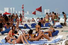 In this March 10, 2012 file photo, people hang out on the beach during spring break in Cancun, Mexico. The beach resort remains a top destination for American spring-breakers seeking an escape from winter. (AP Photo/Israel Leal, File)