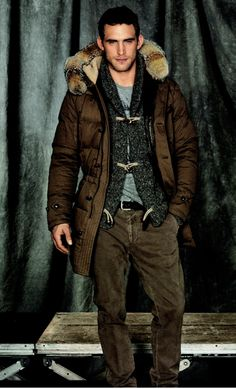 Will Chalker wearing a Fur Trimmed Brown Nylon Parka, Charcoal Tweed Toggle Cardigan, all by Coach. Men's Fall Winter Fashion.