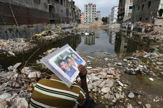 REMEMBERING: Abdur Rahman held a family photo of his wife, Cahyna Akhter, a garment worker who was killed in the Rana Plaza building collapse, as he sits in front of the site in Bangladesh Friday.