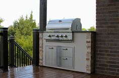 """This custom outdoor kitchen was designed to provide the railing on one side of this new home's deck. The Quivira 32"""" Cheyenne grill head provides three 20,000 BTU burners with 800 square inches of cooking space!    A custom stone and stucco finish to match the home's exterior and ample stainless steel storage round out this awesome outdoor cooking space."""