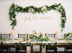 Beautiful garland backdrop for a wedding/party table, with golden hand-writing underneath | Um Doce Dia