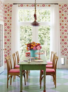 Colourful dining; retro floral wallpaper,  painted diamond check floor and green painted table.