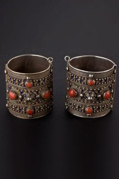 Africa | AMEŠLUH BRACELETS,Silver bracelets decorated with polychrome cloisonné enamel, and bezels of coral. This type of hinged bracelets are worn by women of the Great Kabylie of Algeria. The geometric enamel patterns play around with a coral cabochon | 1st half 1900s.: