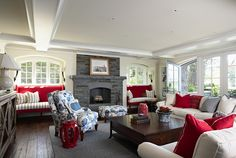 What a great family room! The surprising red with the blue and white fabric gives it punch.