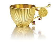A jewelled gold charka, Erik Kollin, St Petersburg, circa 1890, the flared bowl cast with reeds, the double scroll handle set with seven cabochon rubies and inset with a 1 rouble coin, the base with a 2 rouble coin, both of Empress Elizabeth Petrovna and dated 1756.