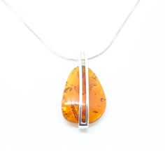 """A very modern, minimalistic design featuring a simple, sterling silver element and a natural Baltic Amber Piece. The necklace includes a 17.5"""" chain made out of sterling silver.The Amber stones have been sculpted for centuries by the everlasting waves of the Baltic Sea, and are hand picked just off the shores of Poland."""