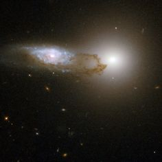 A view of AM 1316-241, made up of two interacting galaxies - a spiral galaxy in front of an elliptical galaxy. The starlight from the background galaxy is partially obscured by the bands and filaments of dust associated with the foreground spiral galaxy.