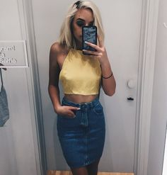 6aebc9c04d4a38 Vlogger Maddi Bragg snaps an She s wearing the California Select Halter Top  and the High Waist Denim Mini Skirt.