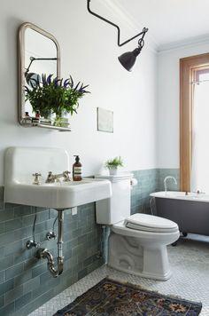 Badezimmer mit blaugrauen Fliesen, freistehende Badewanne und leichtes Boho-Flair durch den Teppich. We Love!