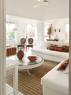 El salón está decorado al detalle con toques en terracota y verde, y objetos y tejidos de artesanía local, en un blanco inmaculado en salón diáfano y luminoso