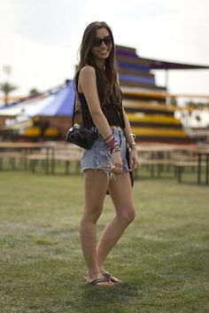 Coachella Festival Style: Simple, yet cute. Here, this festivalgoer paired cutoff shorts with a crop top and oversize sunnies.