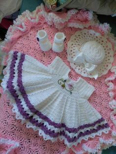 Crocheted white baby dress outfit with purple trim.